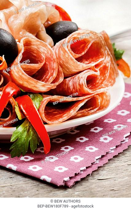 Delicious sliced ham. Party platter of assorted cured meats and olives