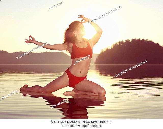 Young woman practicing Hatha yoga on a floating platform in water on the lake during misty morning light, Yoga Pigeon posture variation, Kapotasana