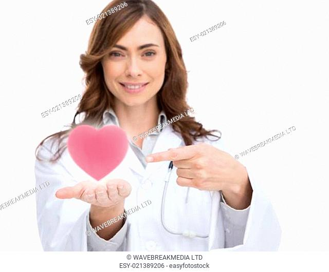 Doctor holding and pointing at a pink heart
