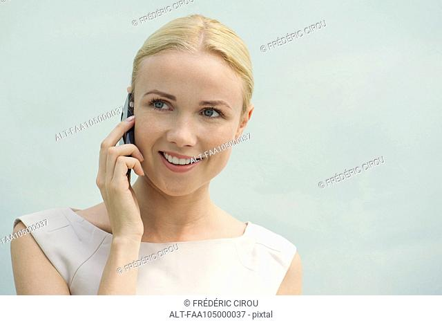Woman using cell phone, smiling