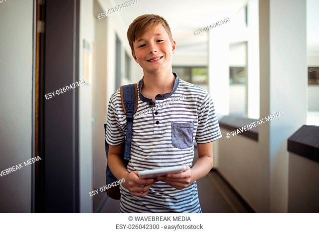 Happy schoolboy using digital tablet in corridor at school