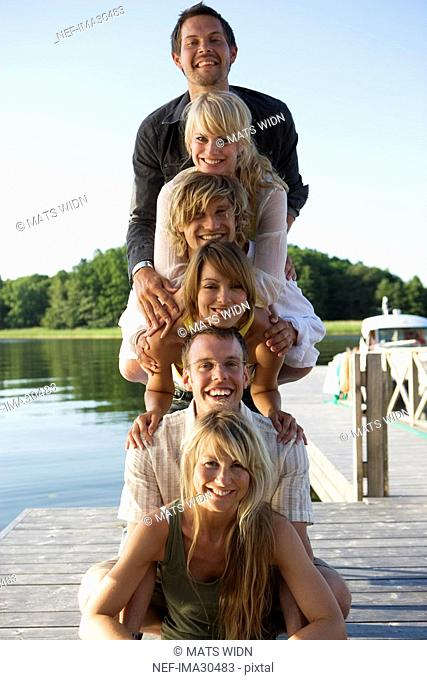 Six people smiling at the camera on a bridge