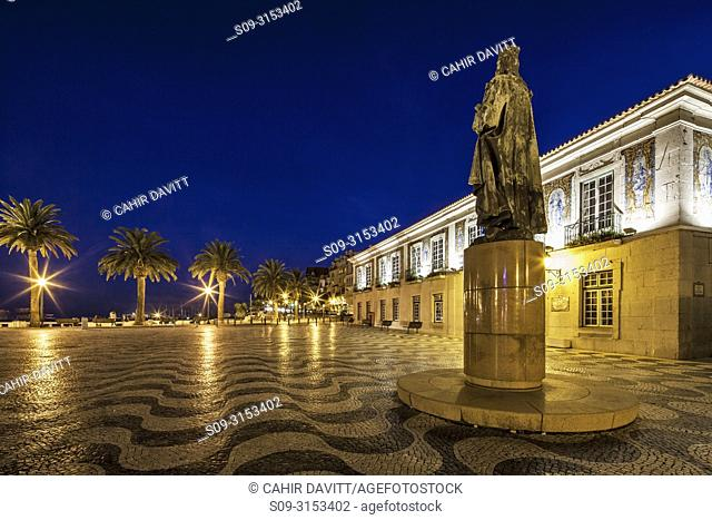 The Camara Municipal de Cascais (Townhall of Cascais) at twilight with traditional Portuguese paving on Praca 5 de Outubro (Town Hall Square) and a statue of...