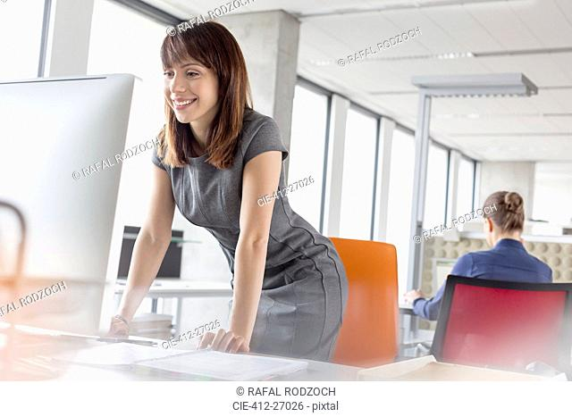 Smiling businesswoman leaning on desk at computer in office