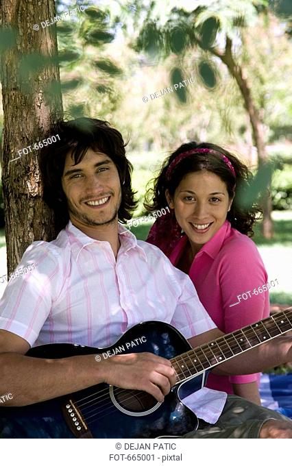 A young couple sitting underneath a tree and playing a guitar