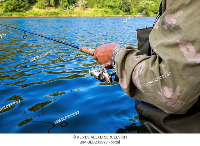 Mari man holding fishing rod in river