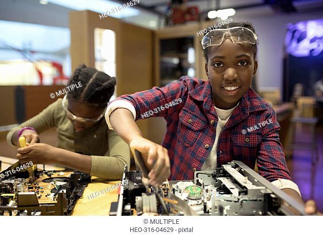 Portrait confident girl assembling electronics in science center workshop
