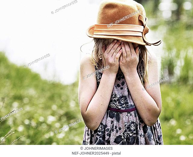 Girl with hands covering face