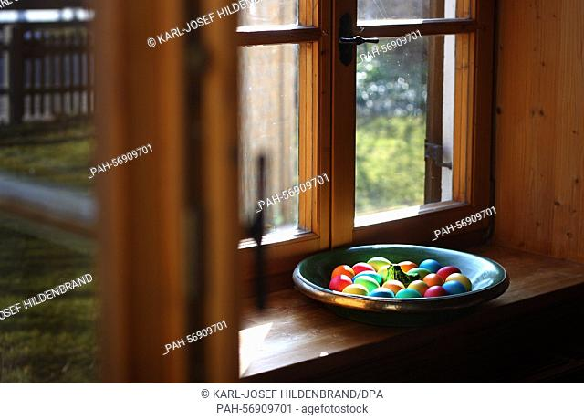 Colourful painted Easter eggs are on display in a bowl on a windowsill of a residential home in Kaufbeuren, Germany, 15 March 2015