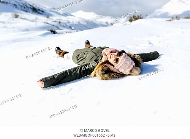Spain, Asturias, playful woman lying in snow