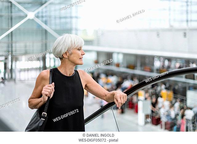 Senior woman on escalator at the airport