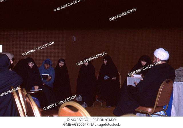 Scene of Muslim women of various ethnicities dressed in chadors, sitting in a circle taking notes, in a ballroom in Iran, March, 1983