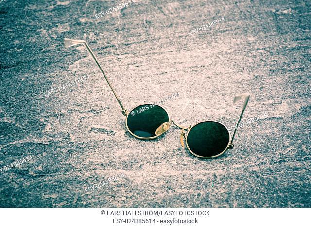 Round sunglasses on stone table, Retro eyewear. Still life of cool design accessory