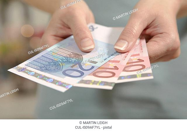 Female hands holding ten and twenty euro notes