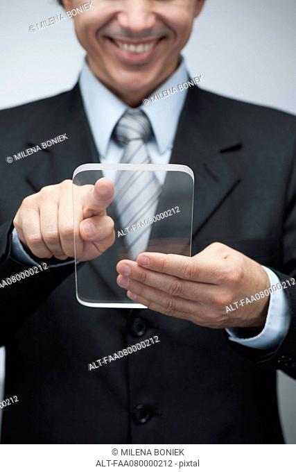 Businessman using transparent digital tablet