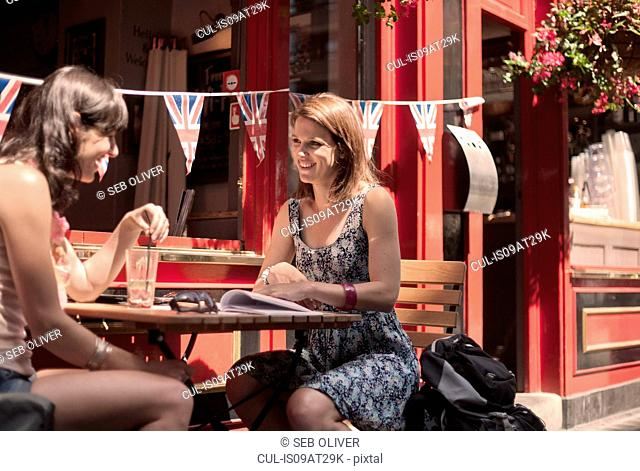 Two women friends guidebook planning outside traditional pub, London UK