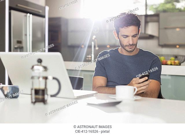 Man texting with cell phone at kitchen table