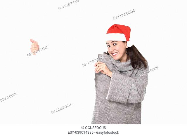 young attractive Hispanic woman wearing Santa Claus Christmas hat and winter jumper holding blank billboard or placard sign as copy space for adding text...