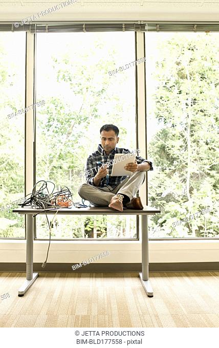Mixed race businessman using digital tablet in empty office