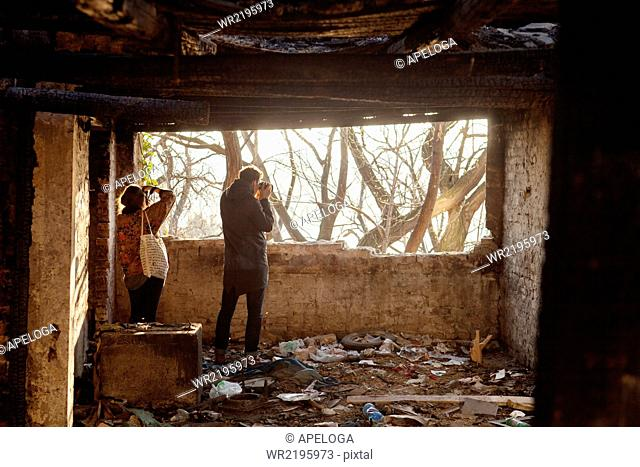 Rear view of man and woman photographing from abandoned building