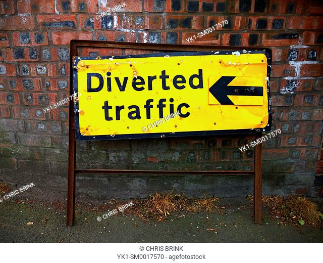 Diverted traffic sign against wall UK