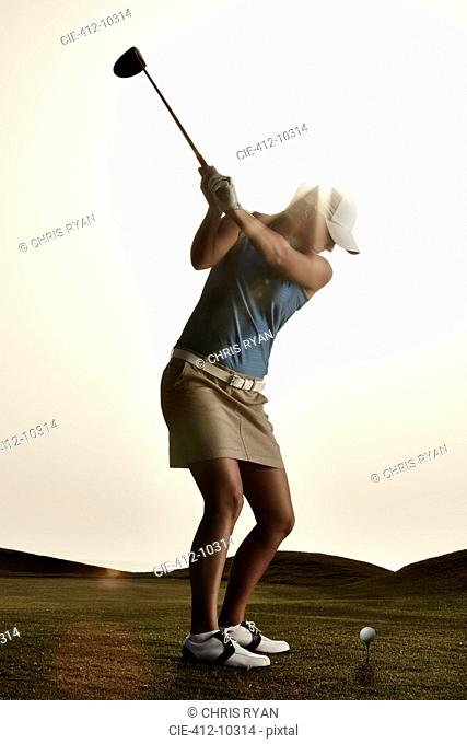 Woman swinging golf club