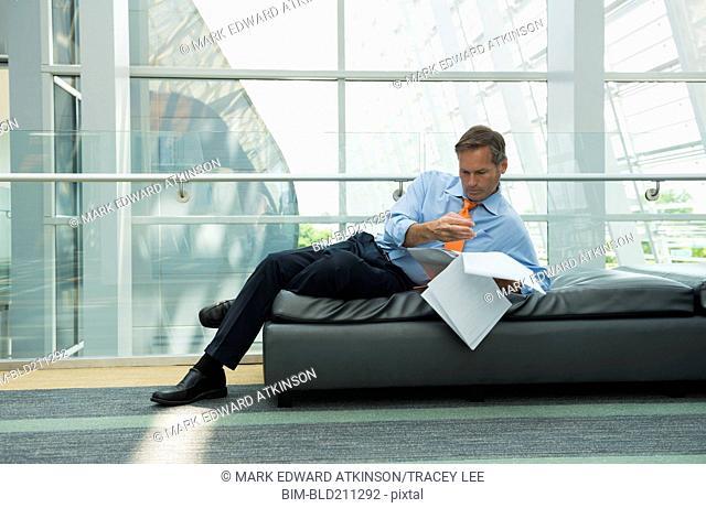 Caucasian businessman reading in lobby area