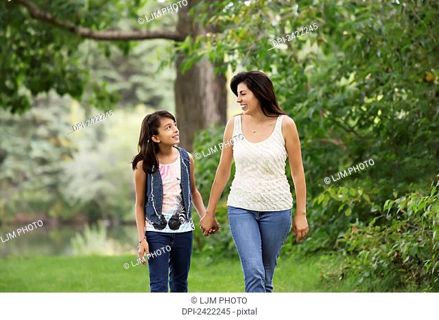 Mother and daughter spending quality time together in a park; Edmonton, Alberta, Canada