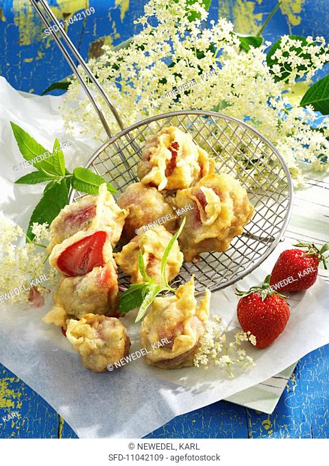 Strawberries in batter with elderflower syrup and lemon balm