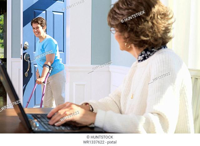 Woman with cerebral palsy coming in through the door and greeting her mother