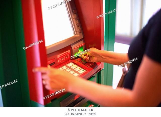 Cropped view of woman withdrawing money from cash machine