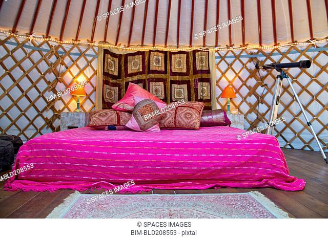 King size bed with bright colors, pillows and telescope inside a Mongolian Yurt, Andalucia, Spain