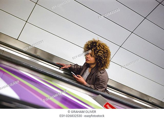 Woman travelling up an escalator from the subway train platform. She is holding a smart phone