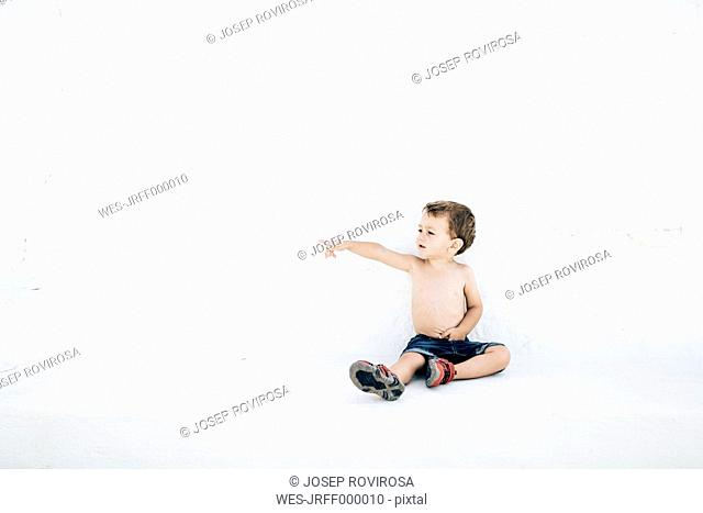Spain, Menorca, shirtless litte boy sitting in front of white wall pointing on something at distance