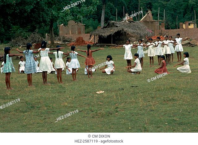 A P.E class in the village of Sigiriya in Sri Lanka. The girl in the centre, facing the camera, is leading her class