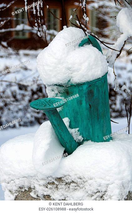 one old watering can on a stone with snow on