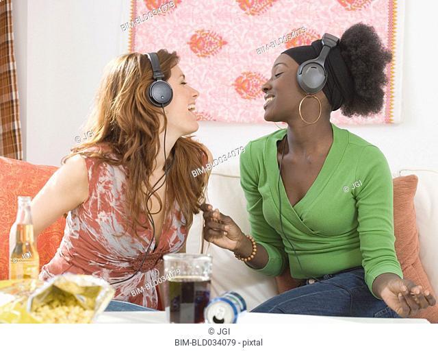 Two women singing to headphones