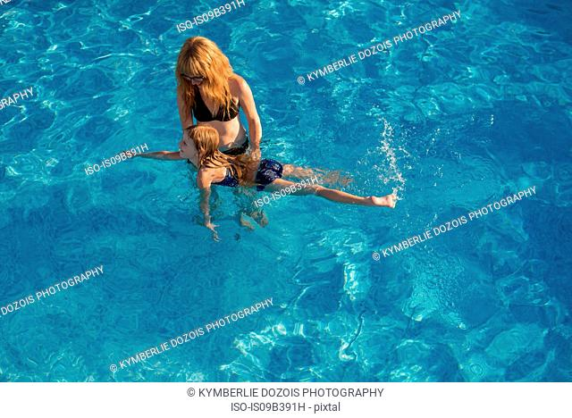 Mother and daughter in swimming pool, mother teacher daughter to swim