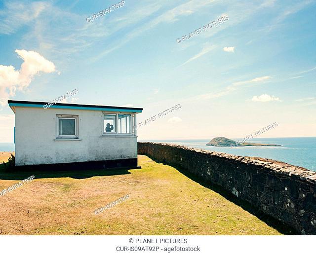 Man looking out from coastal shelter, Mynydd Mawr, Llyn Peninsula, Wales