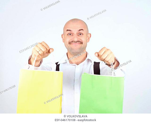 Caucasian man bald, with colorful shopping paper bags isolated on background