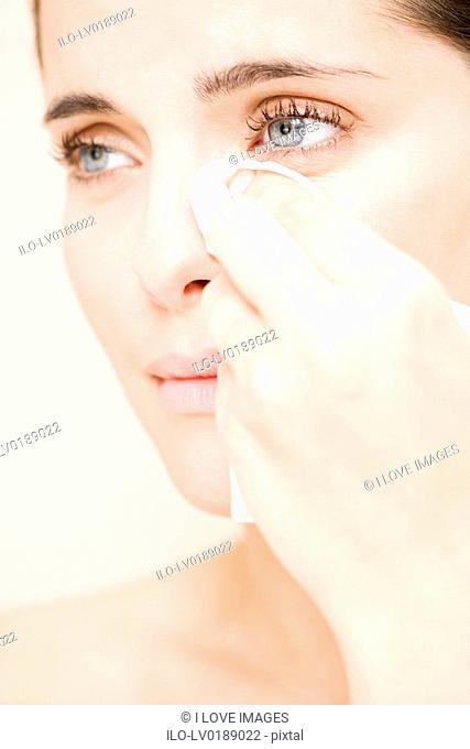 Woman crying, wiping tears away with a tissue