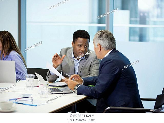 Businessmen discussing paperwork in conference room meeting