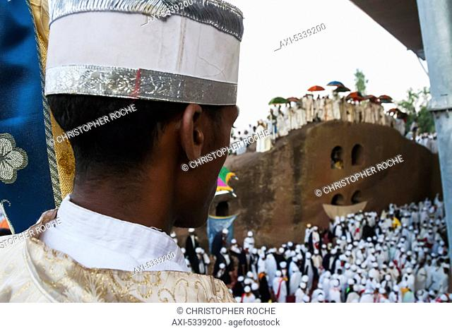 A man with traditional hat and clothing trimmed in silver and gold with a group of people in white garments in the distance; Lalibela, Ethiopia