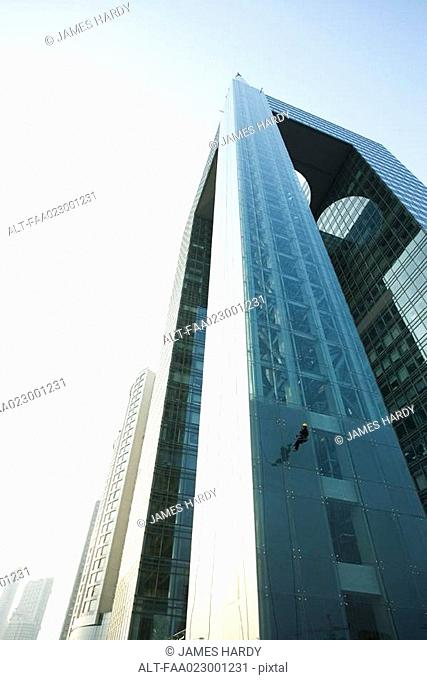 Window washer on side of skyscraper, low angle view