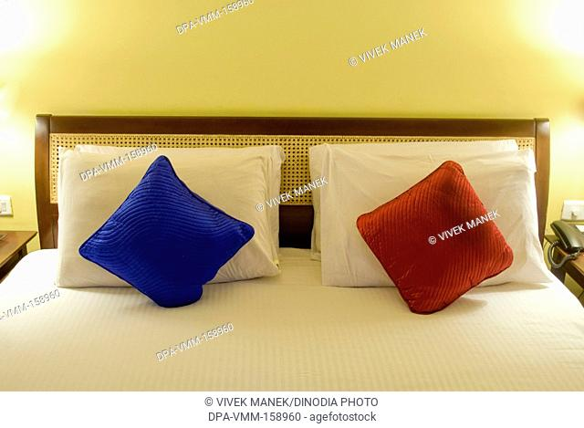 Bed with red white and blue pillows in hotel at Madikeri ; Coorg near Mangalore ; Karnataka ; India