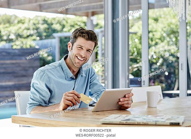Man doing online payment from digital tablet with credit card