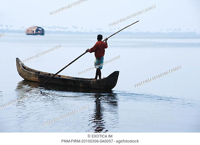 Man rowing a boat in a lagoon, Kerala Backwaters, Alleppey, Alappuzha District, Kerala, India