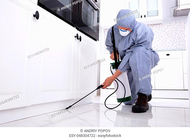 Close-up Of A Pest Control Worker's Hand Spraying Pesticide On White Cabinet