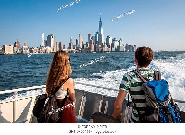 A COUPLE OF TOURISTES CONTEMPLATING THE SKYLINE OF FINANCIAL DISTRICT AND THE BUILDING ONE WORLD TRADE CENTER FROM THE BRIDGE OF A HUDSON RIVER FERRY, MANHATTAN