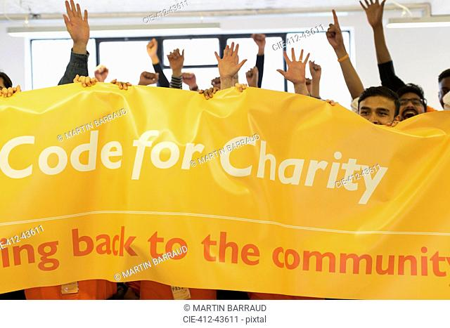 Hackers with banner cheering, coding for charity at hackathon